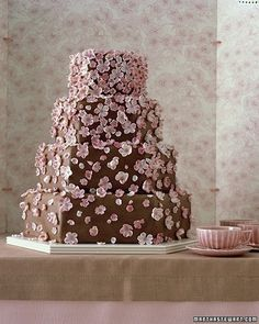This cake reflects a dreamy springtime moment amid the cherry trees, when a breeze scatters the dainty blossoms into the air. Here, they seem to drift from the top of the cake, where they are densely massed, down to the bottom, where the pink petals break apart as they would in nature.
