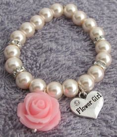 This is a gorgeous flower girl bracelet is made with 8mm Blush Pink pearls silver rhinestones & adorned with rose flower dangling with flower girl charm heart shaped stunning beautiful bracelet adds sophisticated & elegant sparkle to your little girl evening wear & a dazzling addition to a her dress. For custom order please email us or add your custom details in the note with your orderDate Needed by : Color : Age : Charm Choice : with or without Flower Girl CharmFlower Colors Available…