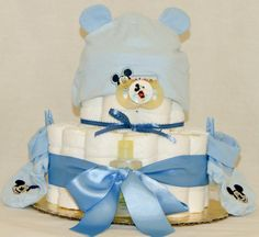 When ordinary just won't do give this Disney themed diaper cake to the next newborn in your life! On sale now $45. Ingredients include: 27 Premium quality Pampers (size 1), Mickey Mouse hat, booties, a bottle and matching binkie. Johnson and Johnson's baby soap, shampoo, lotion and Desitin creme. Embellished with baby cloths pins and matching ribbon. Our cakes do not fall apart, we guarantee satisfaction! To customize your cake contact us on Facebook under Keepsake Diaper Cakes
