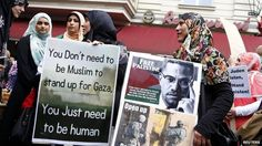 Female Muslim demonstrators hold placards during a protest against the Israeli assault on the Gaza Strip - 25 July 2014