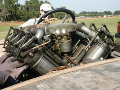 "This is a Curtiss OX-5 ""Hemmi"" cross-flow head engine built in 1918. And looks like pushrod and rocker exhaust with pull-open tube and lever intake. With the pushrod running inside the tube. I'd love to see the valve train at the camshaft."
