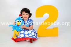 Giovanna fotografando para o painel do aniversário de 2 aninhos no tema da Galinha Pintadinha.