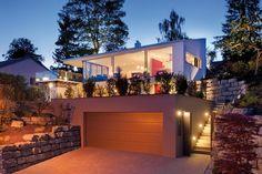 Die in den Hang gebaute Garage fügt sich gut in das architektonische Ensemble ein. Das Flachdach kann als Terrasse oder Gartenfläche dienen. Teckentrup