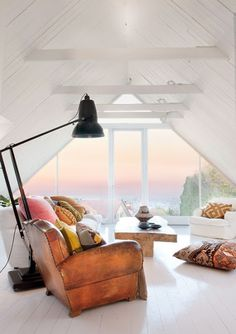 I'm in love with this white attic with vaulted ceiling and a view!