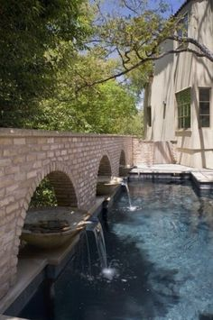 Swimming pool: Bowl fountains sit in brick wall archways,  spilling into pool