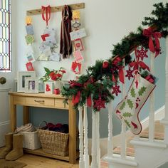 Seasonal Hallway - Ideal Home  Love the garland on the stairs.