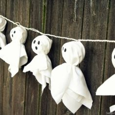 Recycle old lantern lights into Glowing Ghost Garland using fabric, twine and a Sharpie.