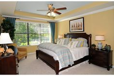 Buttery yellow on the walls and inside the tray ceiling contrast with pale blue bedding. A relaxing master bedroom by Pulte Homes. The Vizcaya community. Jacksonville, FL.