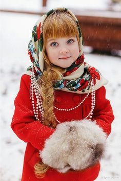 Russian pretty little girl in traditional Russian scarf. Floral scarf Pavlovo Posad scarf. Red coat. Fur. Braid. Winter style for kids.