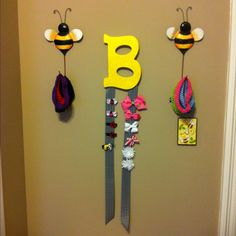 Baby Bow and Headband Hanger- wooden letter painted and sprinkled with glitter. Tack two strips of ribbon on the back of the letter. The Bumblebee headband hangers are actually garden stakes. Bend the iron stake upwards to hang the headbands.