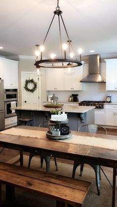 Love the can lights in kitchen, chandelier over table & subway tile on stove wall