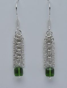 $92.50 A Swarovski cube dangles from a section of 2-in-2 chainmaille surrounded by 2 lengths of sterling silver cable chain. Earwires, headpin and jumprings are handmade with sterling silver. Crystal: Green Swarovski 6mm Cube
