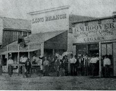 Long Branch Saloon | In 1878 Dodge City's population was less than 1000, yet the town sported 16 saloons. Most renowned was the Long Branch Saloon. Singing, dancing & women were not allowed north of the railroad tracks where the Long Branch was located. Entertainment was provided by owner Chalkley Beeson's five piece orchestra, which later evolved into the famous Dodge City Cowboy Band. Dance halls & saloons south of the tracks offered more lively amusement & back rooms with soiled doves. Old Western Towns, Old West Saloon, Old West Town, Old West Photos, Western Photo, Dodge City, Thing 1, Le Far West, Mountain Man