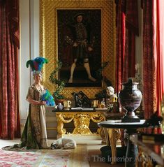 The Dowager Duchess of Devonshire posing for a portrait against a painting of Henry XVIII in the original costume worn by one of her predecessors for a fancy dress ball
