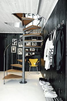 spiral staircase, black walls, photo gallery, and a yellow accent chair.