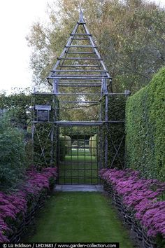 Sedum raised beds line a grass path, hedged allee, hurdles, gate house | Prieure Notre-Dame D'Orsan Story