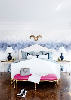 Blue watercolor texture wall treatments, herringbone wood floors, white Hollywood Regency bed, gold French bench with fuchsia cushion, French end tables, cobalt blue lamps and blue paisley bedding | Spazio Rosso