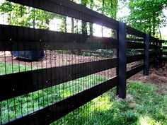 wood 4 rail fence stained black with black vinyl coated welded wire