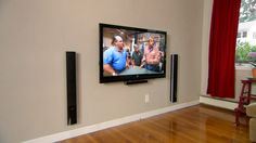 Electrician Scott Caron hangs a flat-screen TV on the wall and conceals all the wiring