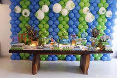 mesa de festa tema mostros sa. Decoração rústica com mesa de madeira e plantas que remetam à pantano. Doces personalizados de mostro. Festa azul e verde.