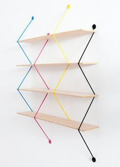 Polish designer Bashko Trybek created 'serpent', a modular shelving system that uses four vivid zigzagging wires as support its wooden planks. since each piece stands alone, the structure becomes adjustable, allowing users to decide on the length, height, and space between the shelves