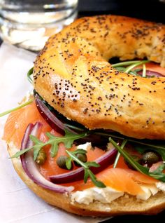 Smoked Salmon Bagel. I like to combine cream cheese with spring onions, capers and pepper. Spread on toasted bagel, add salmon then black pepper and a squeeze of lemon. before adding rocket and red onion on top