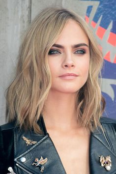 """Ash blonde hair is a sure way to look """"cool"""" this fall. See what we did there? We love how Cara Delevingne lets her cool-tone roots peak through her grayish yellow hue."""