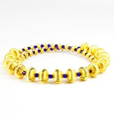 You'll be as bold as it gets in this corrugated gold-plate and Czech cathedral glass choker. Also a great gift for your larger-than-life mom, wife, sister or special friend. This substantial choker features 17 large 10mm hollow gold-plated beads framed by golden spacers and 4mm cobalt blue gold-tipped Czech cathedral glass beads. It is strung on gold-plated memory wire. It's a lavish look sure to be loved by all fans of rich gold and blue. Memory wire is easy to wear and care for. It ...