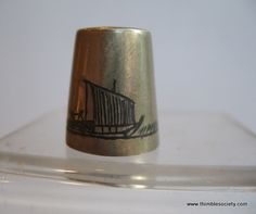 Marsh Arab silver thimble with niello design of a boat sailing in the marsh reeds. With a reed house on reverse.