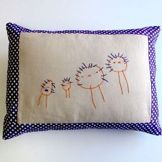Embroidered Family Portrait Pillow - Getting your kids into the artistic spirit is what every crafty mom hopes for. Check out this tutorial to learn how you can get your kids involved in crafting by making an Embroidered Family Portrait Pillow. With this project, you will both make a pillow cover you'll love to display, and you'll show off your kid's handiwork.