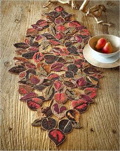 Kim Seybert Laurel Autumn Leaf Table Runner:     Handcrafted table runner, bursting in color from Kim Seybert.     Glass, wood, and plastic beads on cotton backing.    Spot clean.    17.75