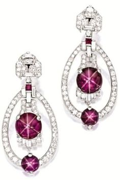 Pair of star ruby and diamond earrings, Yard. Of Art Deco design, each suspending an oscillating cabochon star ruby altogether weighing approximately 6.89 carats, within a frame set with baguette and circular-cut diamonds, highlighted by a similar cabochon star ruby altogether weighing approximately 3.00 carats, to a surmount set with circular-cut, baguette and half moon-shaped diamonds, the diamonds altogether weighing approximately 1.80 carats, mounted in platinum, signed. Via Sotheby's…