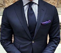 Dark suit navy blue. Tie. Stripe shirt. Pocket square. Single button.