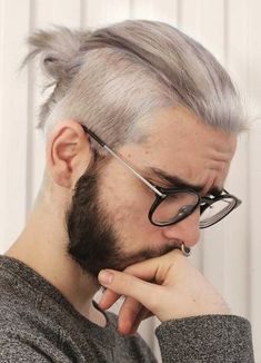 A picture of a male with a great man bun Undercut hairstyle and a hipster beard