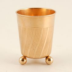 A Fabergé rose gold vodka beaker, workmaster Henrik Wigstrom, St Petersburg, circa 1903-1908, with scratched inventory number 12892. The body decorated with a swirl design emanating from the bottom, resting on three ball feet.
