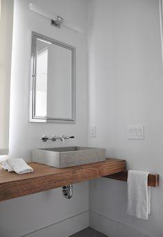 baño rústico con lavabo gris rectangular sobre encimera de madera, espejo como armario empotrado