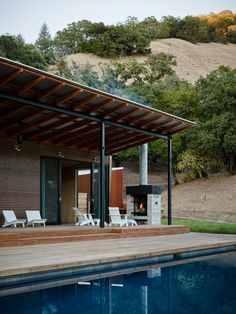 evening-covered-porch-corrugated-metal-roof-pool-wood-deck