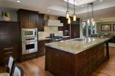 Brown cabinets, mid-tone floor, light counter and light backsplash, natural light from above