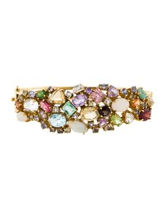 14K yellow gold opal, blue topaz, citrine, emerald, garnet, peridot and pink quartz gemstone cluster bangle with hinged safety plunger clasp closure.  <b>This item has been appraised and inspected by our certified gemologist.</b>  <b>Metal:</b> 14K Yellow Gold <b>Finish:</b> Polished <b>Total Gram Weight:</b> 25.6  <b>Stones:</b> Opal, Blue Topaz, Citrine, Emerald, Garnet, Peridot and Pink Quartz  <b>Cut:</b> Trillion, Oval, Round <b>Color:</b> Green, White, Red, Brown, Pink <b>Clarity:</b…