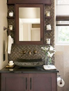 The small shelves along the sides of the mirror are a fantastic way to use void space. I'm obsessed with how the faucet comes out of the wall and the shape of the bowl... and I love the tile... and the cabinet... there really isn't anything I don't like about this vanity! Bravo to the designer!