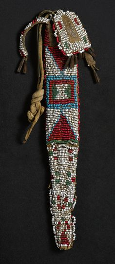 GROUP OF PLAINS BEADED HIDE CASES comprising a Cheyenne fringed strike-a-light, beaded in typical colors against the white glass beadwork ground, decorated with shells, brass beads and other eccentricities, together with a Cheyenne whetstone case, composed of commercial leather, with a cut hide fringed panel trimmed with tin cone pendants, and a Cheyenne or Ute case, perhaps a small tail bag, with beaded flap and tabs at the top.