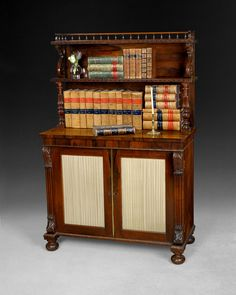 """A very good Regency Period Rosewood Bookcase/Chiffonier with two graduated shelves with a spindle gallery above two doors with pleated silk panels flanked by carved corbels, the whole raised on bun feet . This is very much a Gillows model. Lit: """"Gillows of Lancaster and London"""" by Susan Stuart,  Height: 50"""", Width: 33.75"""", Depth: 15""""."""