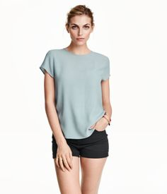 Short-sleeved blouse in crêped woven fabric. Opening at back of neck with button. Rounded hem, slightly longer at back.