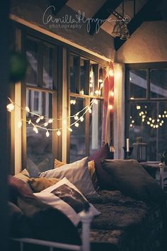 Super cozy porch corner. Love the lights and it all looks so warm and comfortable!