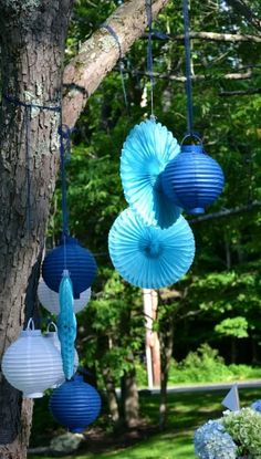 Shades of blue (or any color!) paper lanterns on trees outside or ceiling beams