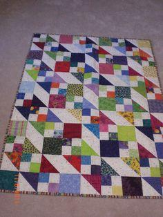 Scrap quilt using half square triangles, square blocks and 4-patch blocks