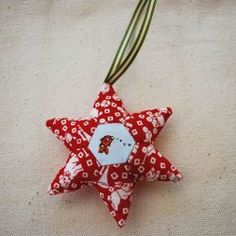 This free quilted ornament pattern is a project you can hand-stitch for any winter holiday. Make this six-pointed, English paper pieced holiday star ornament in red and green for a Christmas ornament or blue and silver for a Hanukkah decoration.