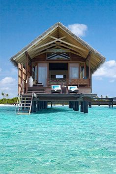 Dream vacation, tropical island romantic get-away, beach destination. Overwater hut on the ocean by the beach- perfect summer spot!