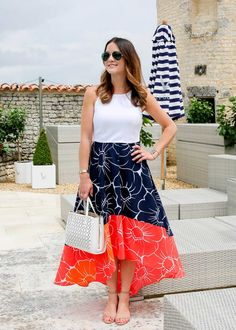 Blogger Jennifer Lake in a floral high low dress by Hutch Designs, a laser cut white crossbody tote and Steve Madden Irenee sandals at Le Logis Grey Goose