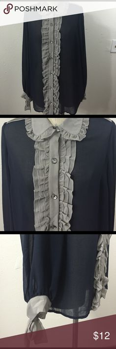 Twelve by Twelve Size XS Blouse with Ruffles Super cute blouse with ruffles down the middle and on collar, button up blouse. Buttons are plastic crystals but really add a nice touch. Fabric is sheer polyester.  Long sleeves have tie bow at the wrist, another special touch. Has a pleat on the back.  Colors are a true navy blue and gray. Really a beautiful blouse! Twelve by Twelve Tops Blouses